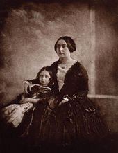 Photograph of a seated young matron (Victoria) cuddling a child next to her