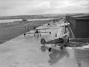 RNAS Hatston - Fairey Swordfish taxi along the tarmac to take off for an exercise with dummy torpedoes from HMS Sparrowhawk, Royal Naval Air Station, Hatston.