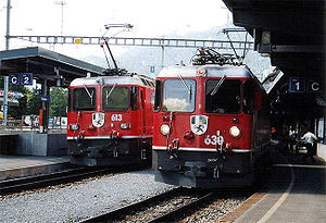 Rhaetian Railway Ge 4/4 II - Two locomotives of class Ge 4/4 II in Klosters. At right, no 630 (Trun) in unrebuilt condition, behind it the already rebuilt no 613 (Domat/Ems) with square headlights and an altered position of the number on its nose.