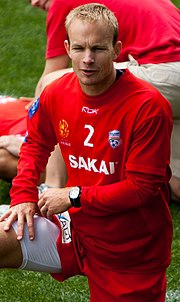 A blond Caucasian man wearing red football kit with his right knee raised.