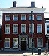 foto van Herenhuis met roodgeverfde lijstgevel. Empire kroonlijst en hardstenen ingangspartij