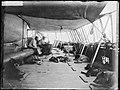 Roald Amundsen ser på Martin Rønne som syr på maskin, 1910 (7675744350).jpg
