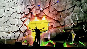 In this scene, Waters punches the wall, while the projections simulate the wall crumbling as a result, revealing a bright sunset behind