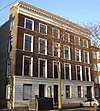 foto van Monumentaal pand met gepleisterde benedenverdieping en bakstenen verdiepingen met hardstenen cordonbanden. Kroonlijst met klossen