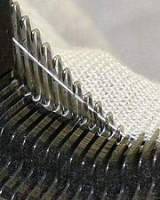 A modern knitting machine in action — knitting machines perform most warp knitting, while weft knitting is generally done by hand.