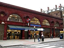 "A red glazed terracotta building. The first storey above ground features four wide, storey-height semi-circular windows with smaller circular windows between above which is a dentil cornice. Below the two right-most windows, the station name, ""Russell Square Station"", is displayed in gold lettering moulded into the terracotta panels. A blue tiled panel above the entrance says ""Underground""."