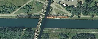 Sault Ste. Marie Bridge Company - The swing bridge portion is shown, retracted to allow the passage of ships in the canal. The other bridge is the highway bridge for vehicle traffic.