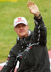 A man in a black jacket and silver cap with his left arm held aloft