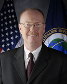 A Caucasian male posing for a professional photo wearing a black suit with a white dress shirt and burgundy tie. A United States flag is seen in the background on the left, while a flag with the globe logo of the National Reconnaissance Office can be seen on the right.
