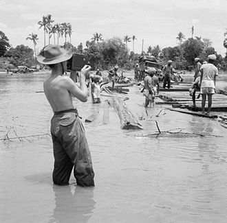 Army Film and Photographic Unit - A member of Number 9 Unit films Indian troops crossing a river during the Burma Campaign 1944–45. Meiktila, Burma ,1945