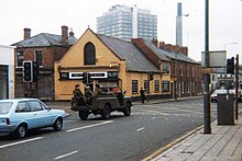 A picture of a city street with an army vehicle in the road.