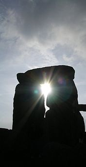 Stonehenge sun through trilith April 2005.jpg