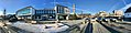 "Stord town hall (rådhus) in Leirvik, Norway. ""Kommunebenken"", parked cars, town square, radio mast tower (antennetårn radiolinjetårn), Borggata, etc. Compressed, distorted panorama 2018-03-10.jpg"