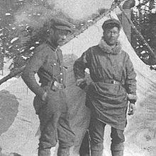 In een grijswaardenfoto staan twee mannen voor een tent en besneeuwde groenblijvende bomen