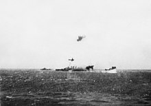 Un ou deux avions attaquant un navire vu de profil, et des explosions au niveau de la mer