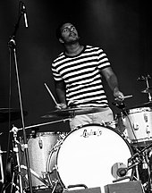 A drummer plays the drums on a stage.