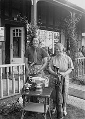 Two lady golfers with trophies outside Llandrindod Wells Golf Club pavilion