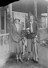 Two lady golfers outside Llandrindod Wells Golf Club pavilion, one holding a cup