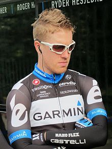 A man in his late twenties wearing a black and white cycling jersey with blue trim, and sun shades.
