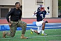 U.S. Marine Corps Maj. Frank L. Moore, the Marine Corps Recruiting Command diversity officer, does lunges with the East Coast Team for the Semper Fidelis All-American Bowl during the second day of practice 130101-M-EK802-467.jpg