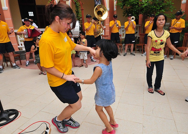 File:U.S. Navy Cryptologic Technician Technical 3rd Class Emily Garcia-Delgado dances with a child at the Thanh Tam Special School while members of the U.S. 7th Fleet Band ensemble Orient Express perform in Da Nang 110717-N-XR557-090.jpg