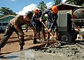 US Navy 070604-N-2296G-051 Builder 2nd Class Michael Schneider (left) attached to Naval Mobile Construction Battalion (NMCB) 7, rakes concrete with his Philippines Navy seabee counterpart, Fireman 1st Class Builder Elmer Ang.jpg