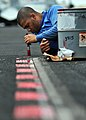 US Navy 080903-N-7981E-040 Aviation Boatswain's Mate (Handling) 3rd Class Damien Clines, from Los Angeles, Calif., repaints weapons elevator safety lines on the flight deck of the Nimitz-class aircraft carrier USS Abraham Linco.jpg