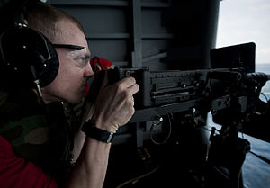 US Navy 120103-N-DR144-188 Aviation Ordnanceman 3rd Class Christopher Crone fires a .50-caliber machine gun during a crew-served weapons fire exerc.jpg