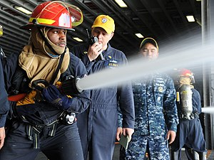 US Navy 120104-N-EK905-043 Electrician's Mate Fireman Emmett Brown trains as number one nozzleman during a general quarters drill in the hangar bay.jpg