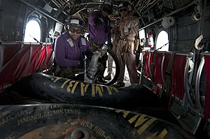 US Navy 120209-N-PB383-157 Aviation Boatswain's Mate (Fuels) Airman Edwin Montanez refills a fuel bag inside a CH-46E Sea Knight helicopter.jpg