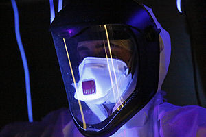 A person wearing full protective gear, glowing in ultraviolet light