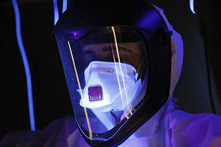 After a training exercise involving fake body fluids, a healthcare worker's personal protective equipment is checked with ultraviolet light to find invisible drops of fluids. These fluids could contain deadly viruses or other contamination. Ultra-violet screening for potentially Ebola-carrying liquids (15811190376).jpg