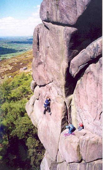 Climbing - Rock climbers on Valkyrie at The Roaches in Staffordshire, England.