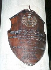 A white, cylindrical stone is marked with a copper-colored shield marking the burial place of Van Rensselaer, which includes Dutch text.
