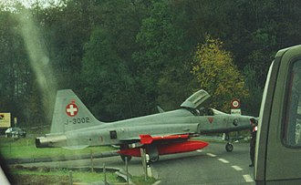 Motorways of Switzerland - A Swiss Air Force F-5E Tiger II crossing a road between the runway and an Hardened aircraft shelter in Mollis airfield in 1999.