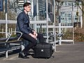Young male waiting in the bus stations of a train station in Reading, UK.jpg