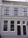 foto van Huis met gebosseerd gepleisterde gevel met kroonlijst op consoles die voortzetting is van die van nr 64