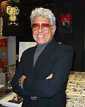 photo couleur d'un homme souriant cadré plan rapproché taille