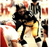"American football quarterback, Terry Bradshaw, prepares to receive a snap. He is wearing a black Pittsburgh Steelers jersey with a white number ""12"" and gold pants."