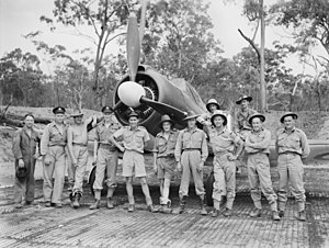 Twelve men wearing military uniforms standing in front of a single-engined World War II-era propeller fighter aircraft