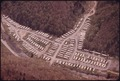 AERIAL VIEW OF CLUSTERED MOBILE HOMES USED BY FAMILIES WHOSE HOUSING WAS WIPED OUT IN THE EARLY 1970'S WHEN AN... - NARA - 556476.tif