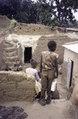 ASC Leiden - van Achterberg Collection - 5 - 006 - Quatre petits enfants en sandales vus de dos entre des murs bas en argile - Bobo-Dioulasso, Burkina Faso, 19-26 août 2001.tif