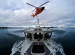 A 45-foot Response Boat-Medium from Coast Guard Station Seattle and an MH-65 dolphin helicopter from Coast Guard Air Station Port Angeles conduct hoisting training (32172987830).jpg