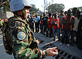 A United Nations (UN) peacekeeper from Argentina talks to men waiting for their female family members 100216-N-HX866-009.jpg