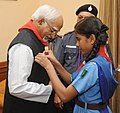 A cadet of Scouts and Guides pining flag to the Vice President, Shri Mohd. Hamid Ansari, on the occasion of Bharat Scouts & Guides Flag Day, in New Delhi on November 10, 2014.jpg