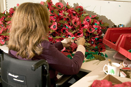 A volunteer makes red remembrance poppies at the Royal British Legion Poppy Factory in London, where over 30 million poppies are made by a small team each year A volunteer constructs poppies at the Royal British Legion Poppy Factory, Richmond MOD 45148164.jpg