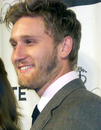 A 27-year old, dark-haired, bearded man, smiling to the left of the camera.