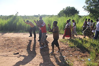 Community-led total sanitation - Villagers making a transect walk or 'walk of shame' to the open defecation places, singing 'let us end open defecation' (village near Lake Malawi, Malawi)