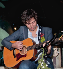 A dark-haired man sitting down playing guitar.