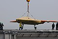 An X-47B is loaded onto flight deck of USS George H.W. Bush. (8721189800).jpg